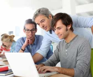 Man Looks Over Interns Shoulder While On Computer Picture
