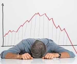 Frustrated man with head on desk sitting in front of a downward trending graph
