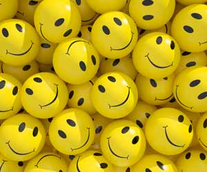 A collection of yellow balls with smiley faces on them.