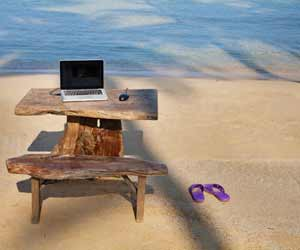 Flexible work station with laptop on wooden desk at beach.