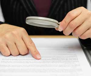 Paralegal scanning an employment contract with a magnifying glass