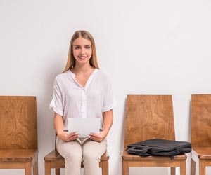 Female job candidate waiting for interview with a bag of things